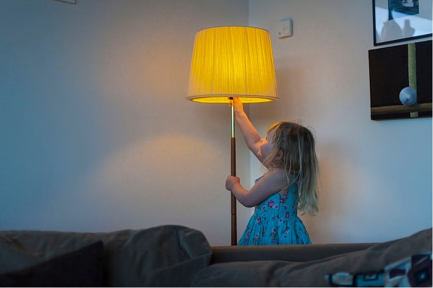 a girl switch on a lamp in living room